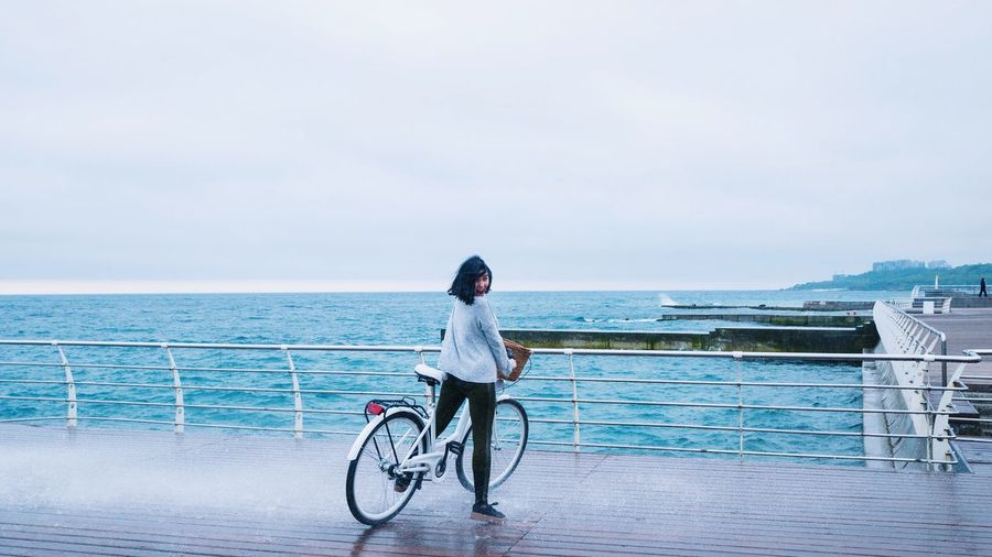 Woman with bicycle standing on promenade against sky