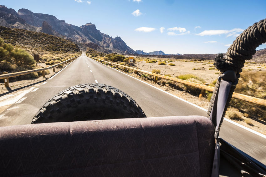 back view from open off road car to a long road in the desert Discovering El Teide National Parc Freedom Vacations Wheel Backview Beauty In Nature Blue Sky Day Desert Landscape Direction Landscape Mountain Mountain Range Nature No People Off Road Car Outdoors Road Scenics Sky Sunny Day The Way Forward Transportation Traveler Walking