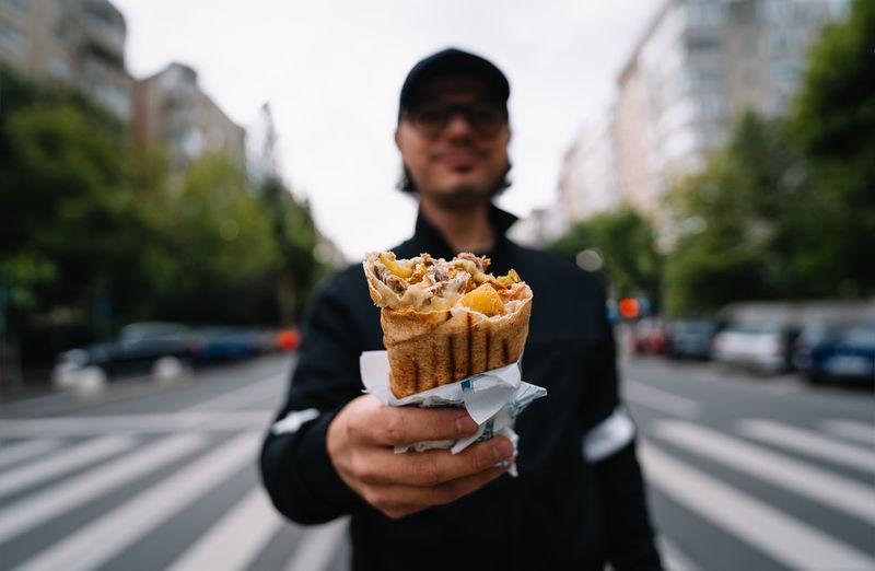 Man holding kebab sandwich wrap on street