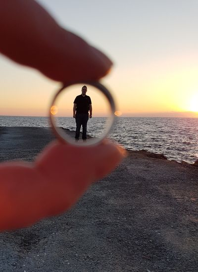 Cropped Hand Of Woman Holding Ring Against Boyfriend At Beach