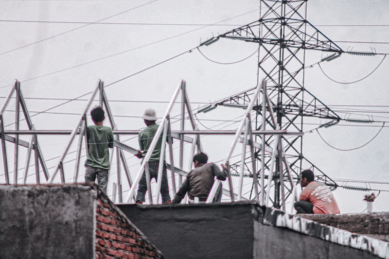 People working by electricity pylon against sky