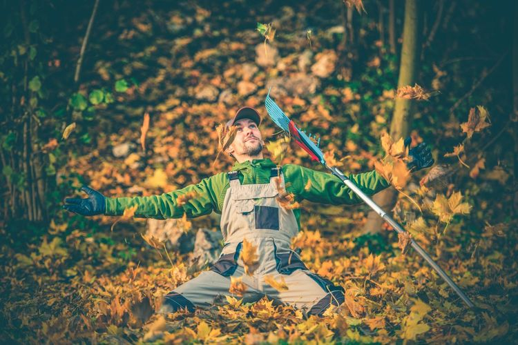 Mid adult man with arms outstretched kneeling on autumn leaves by gardening fork