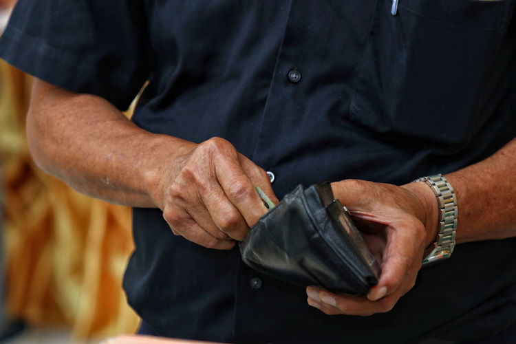 Midsection of man holding wallet