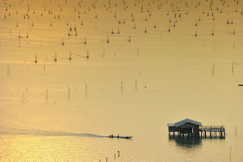 High angle view of stilt house over sea during sunset