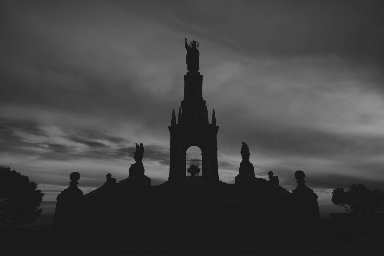 cloud - sky, sky, religion, statue, built structure, sculpture, spirituality, architecture, low angle view, place of worship, silhouette, travel destinations, building exterior, day, outdoors, no people