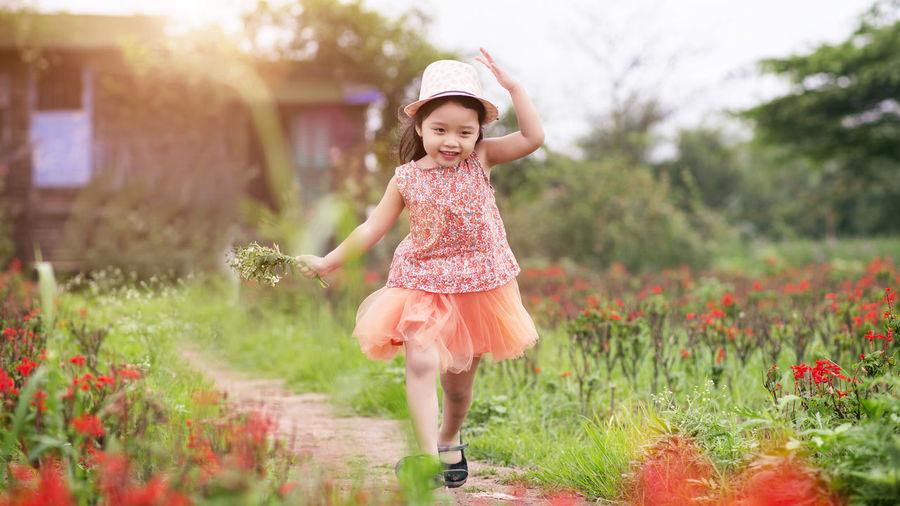 Full length of happy girl in garden