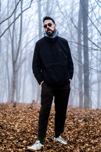 Full length of man standing in forest during winter