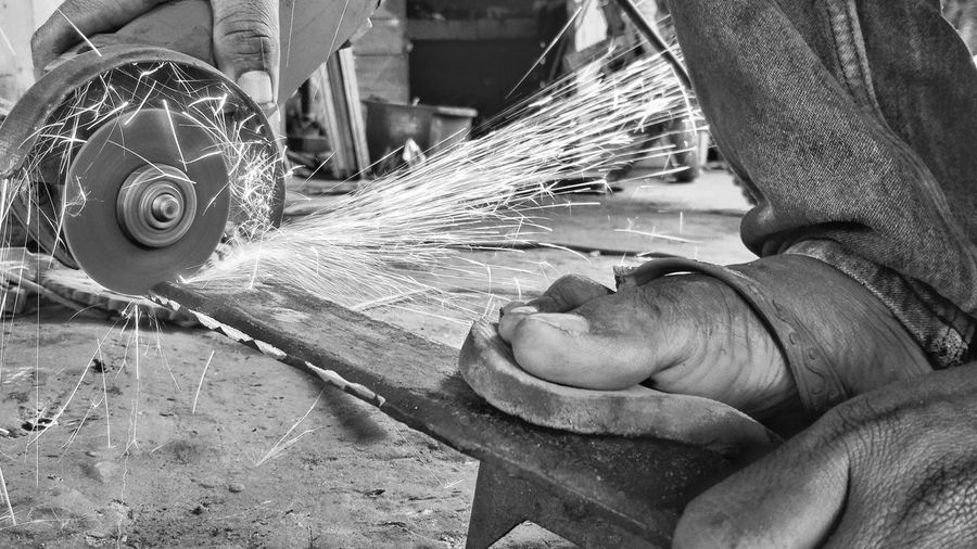 Low section of worker cutting metal at workshop