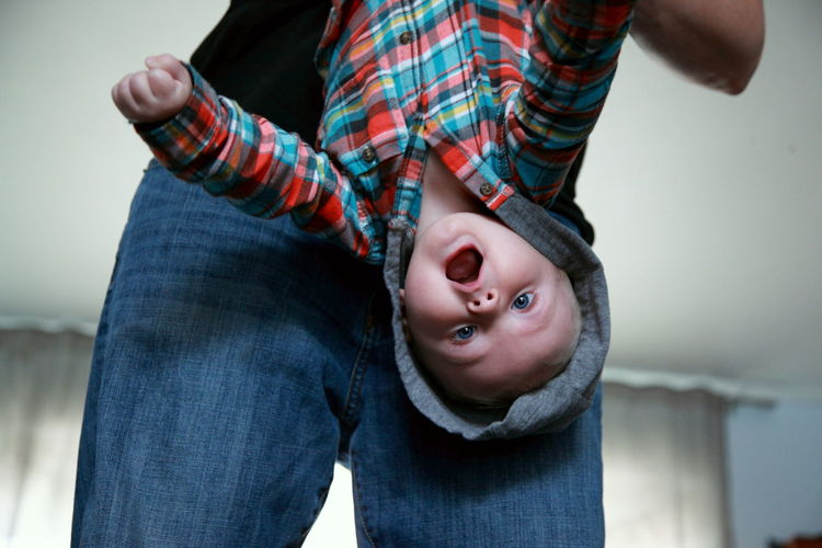 Midsection of woman holding baby boy at home