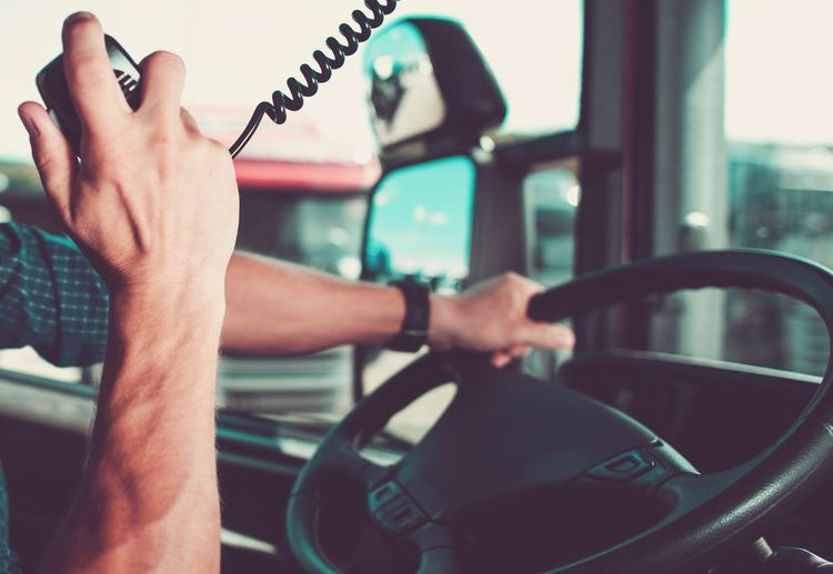 Cropped Hand Holding Radio Walkie Talkie While Driving Truck