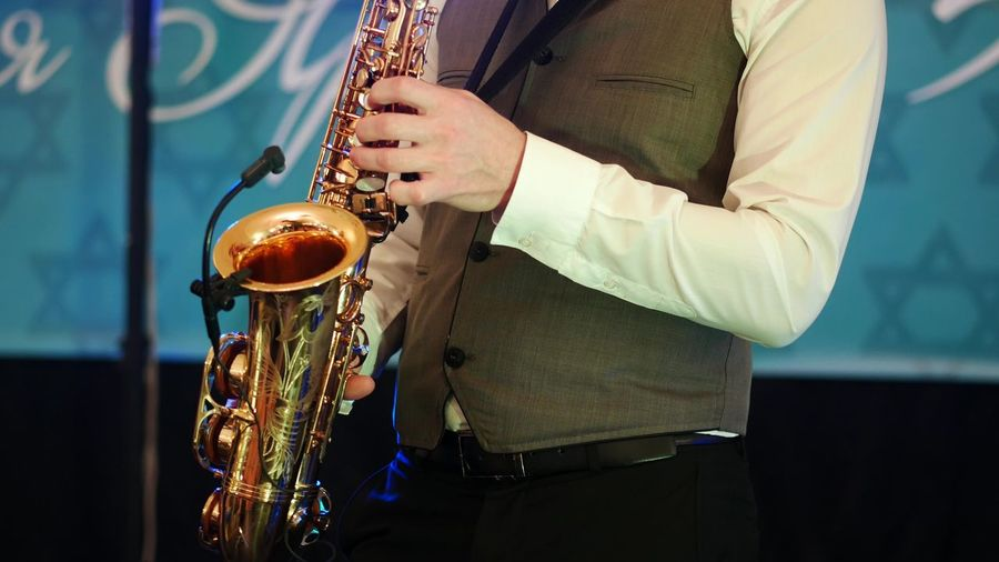Midsection Of Man Playing Saxophone Against Wall