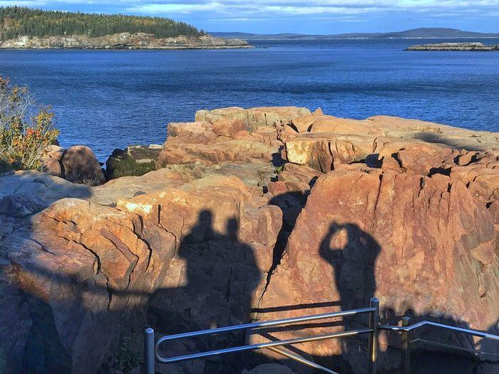 Shadow of people on rocks by sea