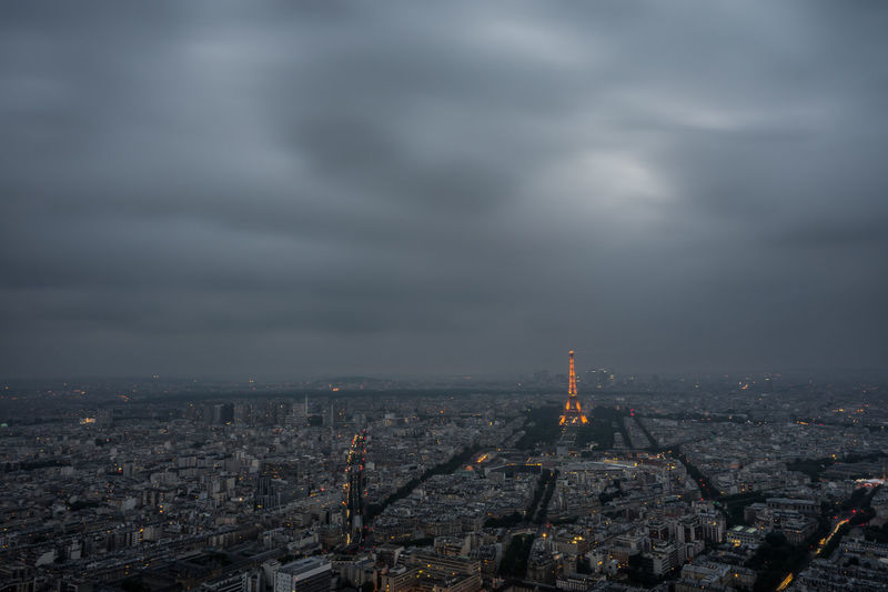 Distant View Of Eiffel Tower Amidst Cityscape Against Cloudy Sky At Dusk