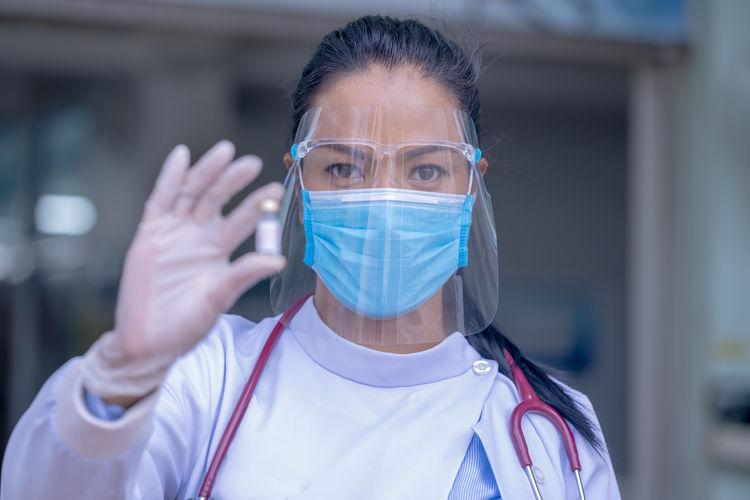 Portrait of female doctor wearing mask holding vial