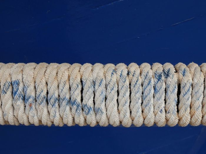 Close-up of rolled rope on blue boat