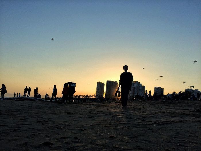 Silhouette people at beach against clear sky during sunset
