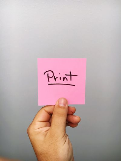 Cropped Hand Of Person Holding Print Text On Adhesive Note Against Gray Background