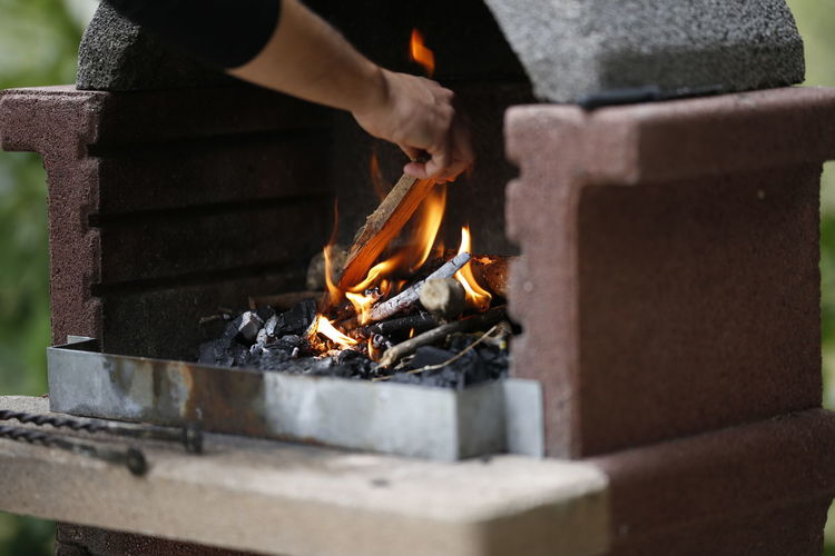 Midsection of man putting firewood in fireplace outdoors