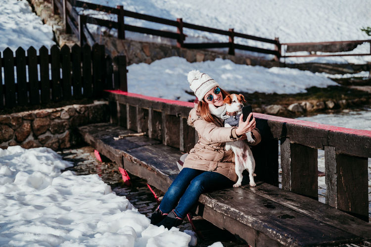 Woman taking selfie with dog while sitting on bench amidst snow covered field