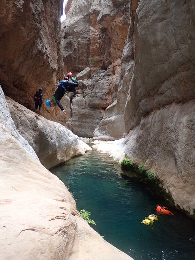 Man jumping in river amidst rock formations