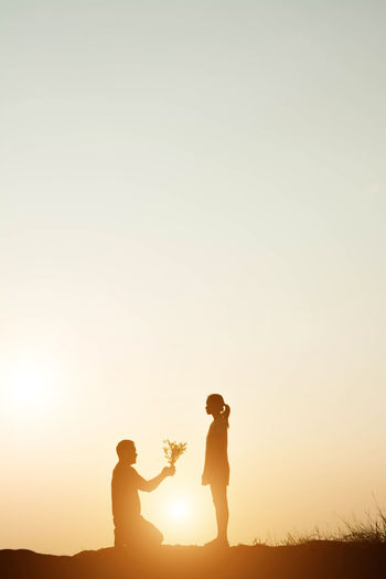 Silhouette man proposing woman against sky during sunset