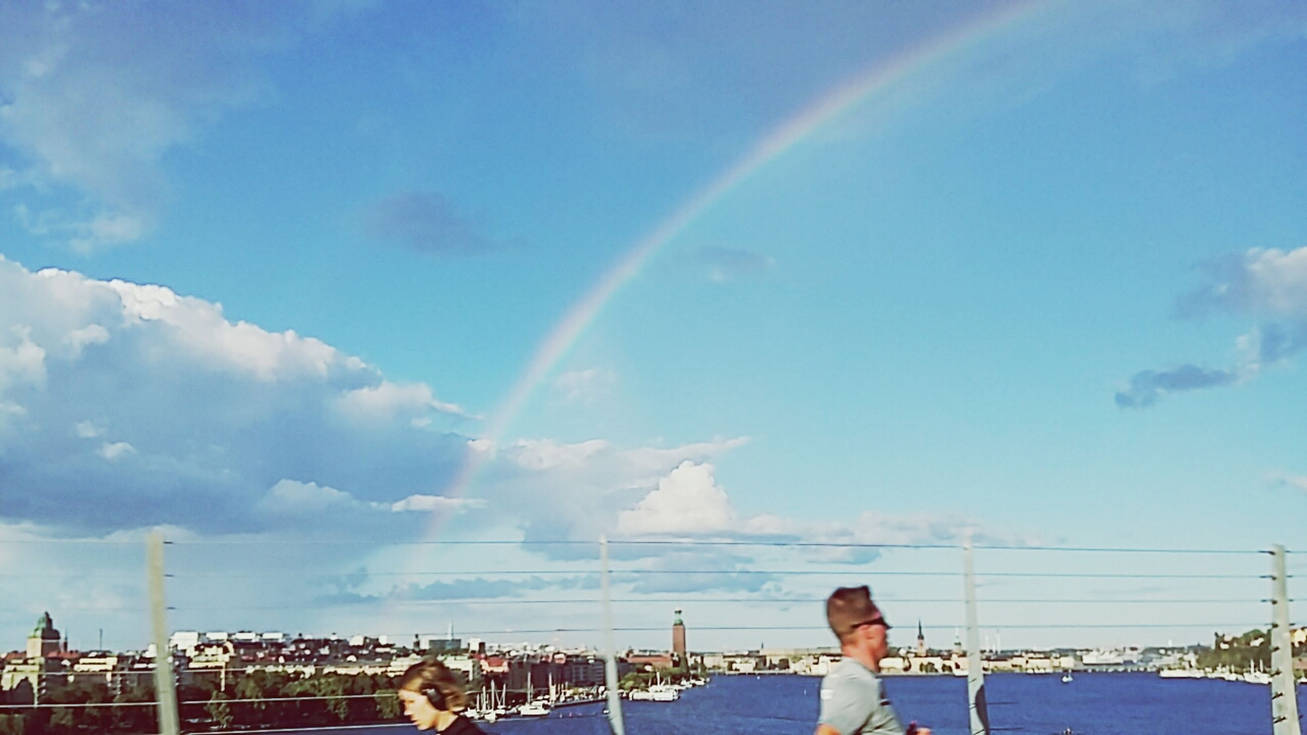 rainbow, building exterior, sky, multi colored, built structure, city, architecture, blue, cityscape, townscape, cloud - sky, day, cloud, town, residential district, housing settlement, development, beauty in nature, nature, outdoors, city life, ocean