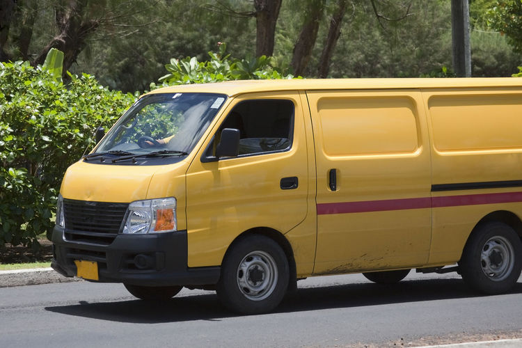 Delivery Van Driving - Rarotonga, Cook Islands, Polynesia, Oceania Driving on the move Van Delivery Delivery Van Traffic Close-up Side View Dhl Road Street Express Single Object Business Finance And Industry Economy Worldwide Left-hand Driving Driver Sitting Unrecognizable Person One Person Cook Islands Tropical Climate Business Transportation Mode Of Transportation Motor Vehicle Land Vehicle Car Tree Day Outdoors Yellow Travel Nature
