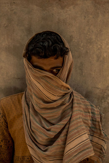 Man with face wrapped in scarf looking away against wall