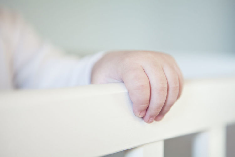 Cropped Hand Of Baby Holding Crib At Home