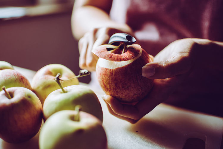 Midsection Of Woman Peeling Apples