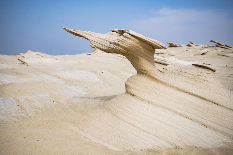 Rock formation on desert against sky