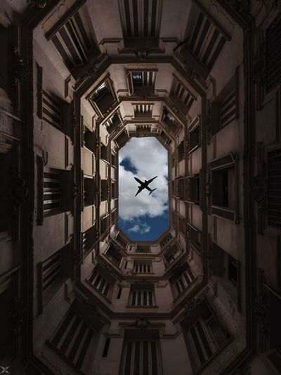 Low angle view of airplane seen through buildings