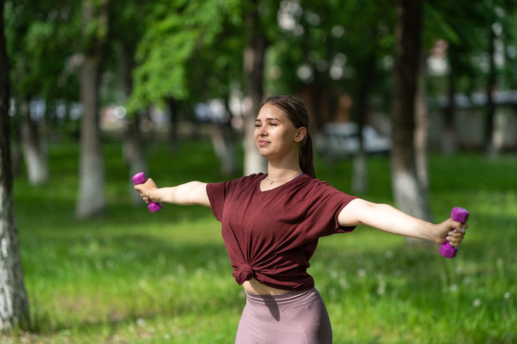 Young woman with arms raised standing on field