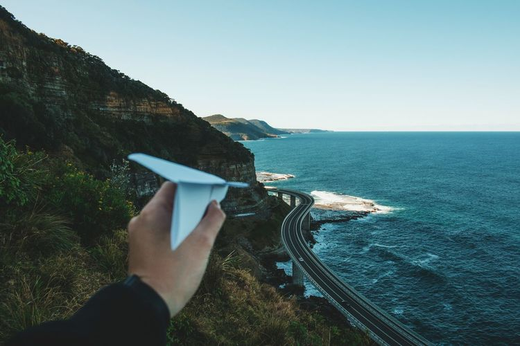 Cropped image of hand holding paper airplane against sea