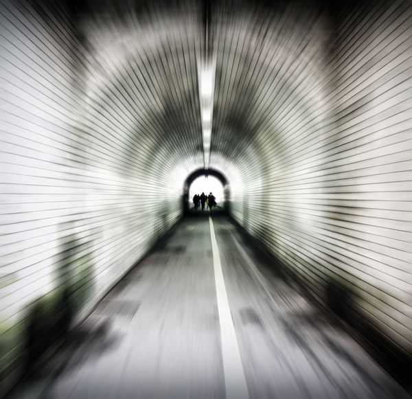 zoom blur image of an old dark pedestrian tunnel with unidentifiable people emerging into the light Tunnel Pedestrian Blurred Motion Zoom Blur Underground Walkway Abstract Motion Illuminated Diminishing Perspective Subway Walking on the move Concept