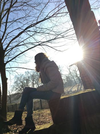 The City Light young adult Full Length Lens Flare Sitting Sunlight Side View One Person Back Lit Tree Outdoors Day Leisure Activity People Adults Only Sunbeam Adult Real People Young Adult Nature