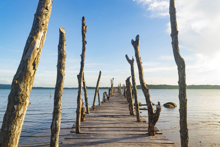 Backgrounds Wooden Wood - Material Bridge - Man Made Structure Day Freshness Outdoors Seascape Water Sea Beach Sky Horizon Over Water Cloud - Sky Wooden Post Pier Shore Jetty Calm Wood Paneling Mooring Post Stilt House Moored Underneath Boardwalk Diminishing Perspective