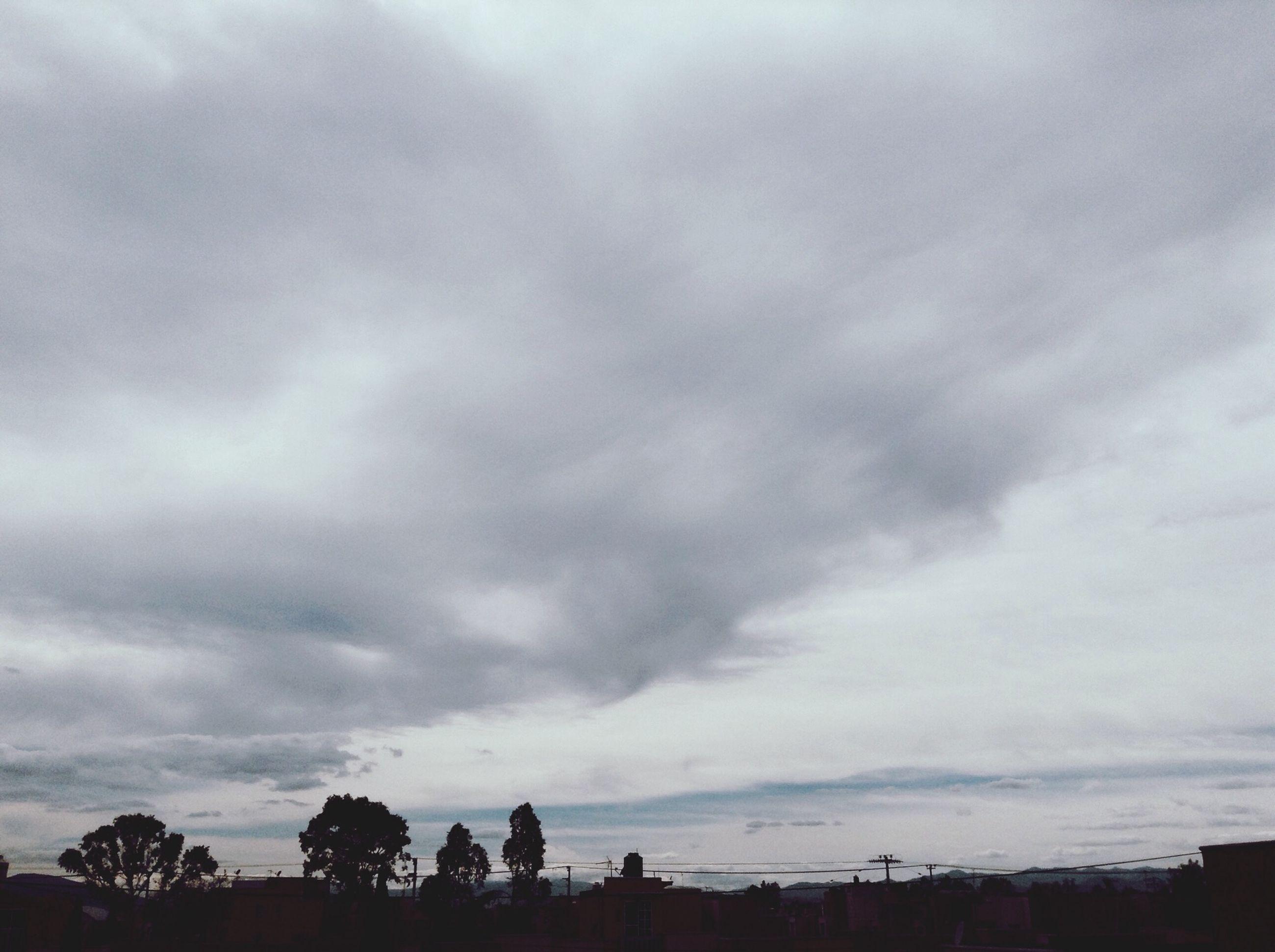 sky, cloud - sky, cloudy, tree, weather, silhouette, overcast, tranquility, beauty in nature, tranquil scene, scenics, nature, cloud, dusk, landscape, building exterior, built structure, cloudscape, storm cloud, outdoors