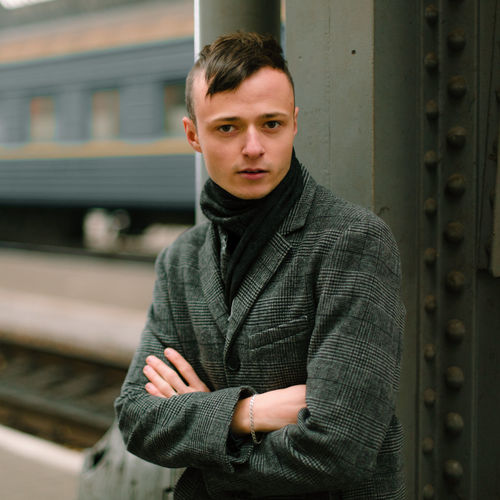young man with a short hairstyle in a gray coat with black jackfoot posing at the train station, cold weather, men's style, street photography One Person Young Man Man Men Protrait Railway Station Call Box Payphone Call Train Gray Coat Coat Black Scarf Fashion Model Look Emotions Happiness Venom Sitting Blackandwhite Cold Weather Gangster Mafia  Close Up Portrait Of A Man  Business Style