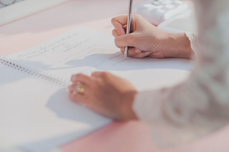 Close-up of bride signing paper on table