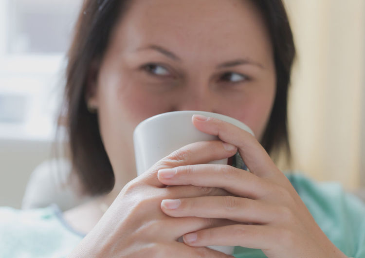 Close-Up Of Young Woman Looking Away While Having Coffee