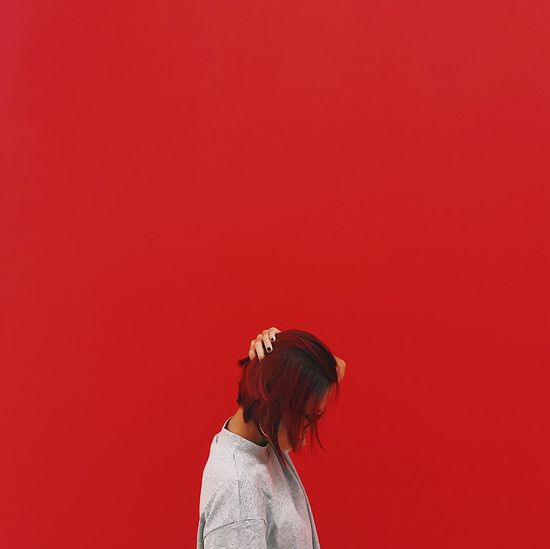 Woman Standing Against Red Background