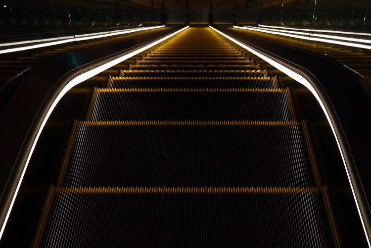 Dark Shadows & Lights Architecture Built Structure Diminishing Perspective Direction Escalator High Angle View Illuminated Indoors  Motion Moving Walkway  No People Pattern Railing Shadow Staircase Steps And Staircases The Way Forward Walkway Stairway