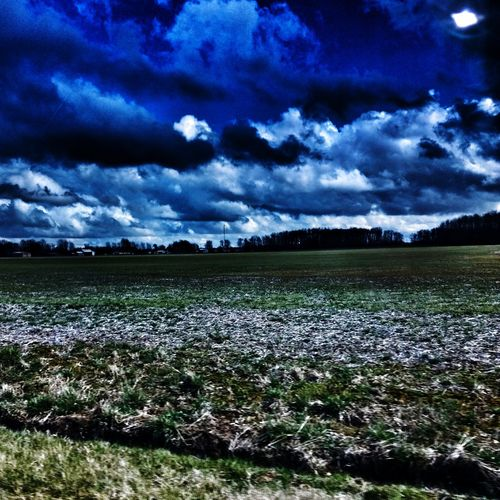 View of field against cloudy sky