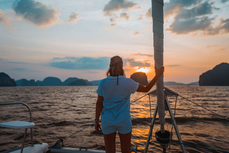 Rear View Water One Person Sea Real People Sunset Sky Lifestyles Beauty In Nature Scenics - Nature Standing Beach Women Leisure Activity Cloud - Sky Land Casual Clothing Nature Outdoors Hairstyle Looking At View