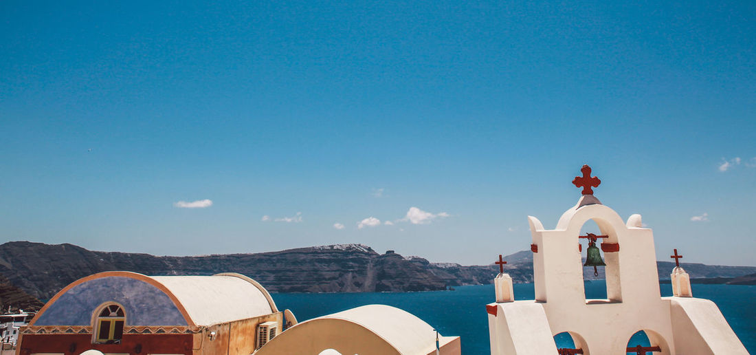 High section of church by sea against blue sky at oia