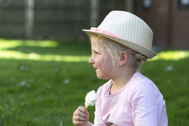 Cute blonde girl eating ice cream outside in the garden At Home Baby Eating Green Hanging Out Happiness Happy Hat Ice Lifestyle Bayern Blond Cute Garden Girl Ice Cream Meadow Outdoors Smiling Springtime Summer Sun Hat Sweets Toddler  Toddlerlife
