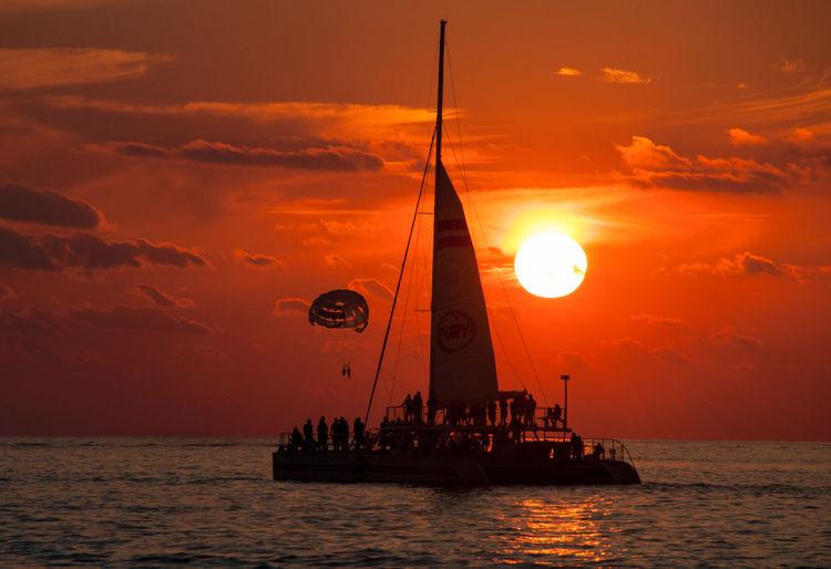 Sailboat on sea with parachute at dusk