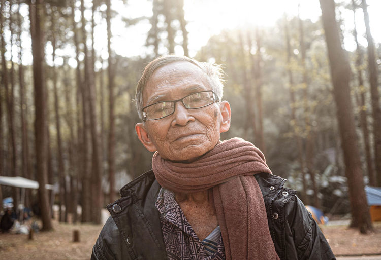 Portrait of senior man wearing scarf against trees