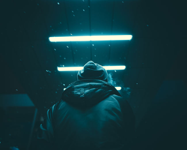 Man standing in blue light. Rear View One Person Night Men Real People Illuminated Lifestyles Leisure Activity Indoors  Waist Up Lighting Equipment Architecture Dark Headshot Standing Arts Culture And Entertainment Light - Natural Phenomenon Underwater Nightlife